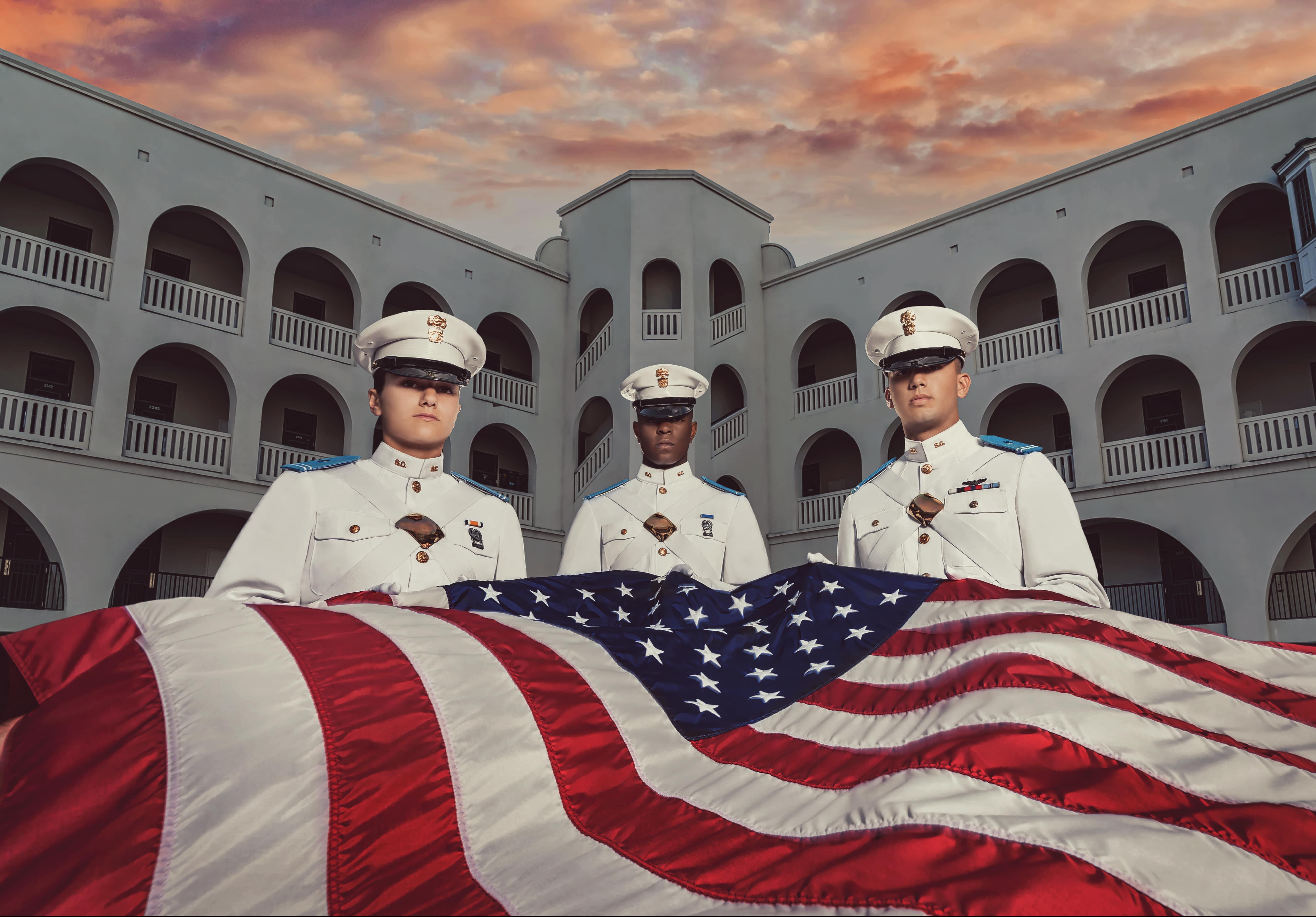 Citadel cadets holding american flag in barracks